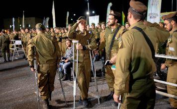 Un soldado herido de Israel hace un saludo militar entre un grupo de soldados adicionales y oficiales
