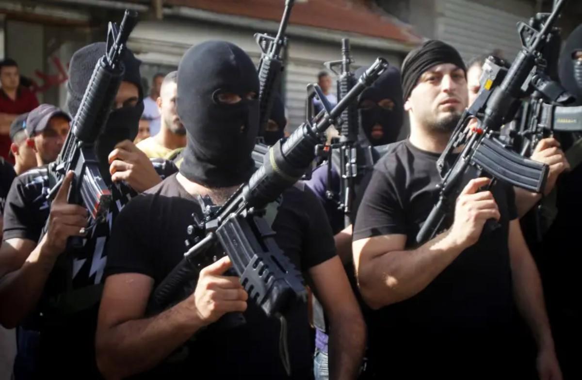 hombres jovenes y fuertes , algunos con la cara tapada, empuñando un arma pesada y vestidos de negro
