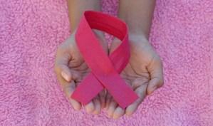 Un par de manos sostienen el símbolo internacional de la lucha contra el cáncer de mama