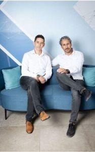 dos hombres de panatlón gris y camisa blanca con las piernas cruzadas, sentados en un sofá azul claro