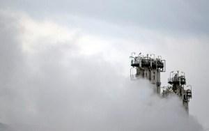 la mayor parte de la imagen está cubierta por una espesa niebla, a la derecha asoman dos torres de alguna infraestructura