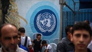 emblema de la UNRWA pintado en la pared, ciertas personas delante