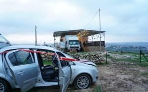 coche estacionado en campo abierto frente a una casa provisional