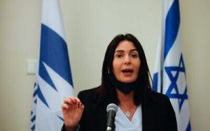 mujer de pelo largo y negro habla ante un micrófono con dos banderas de Israel a su espalda