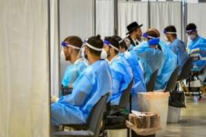 hilera de varones jóvenes con protección completa antivirus, sentados esperando