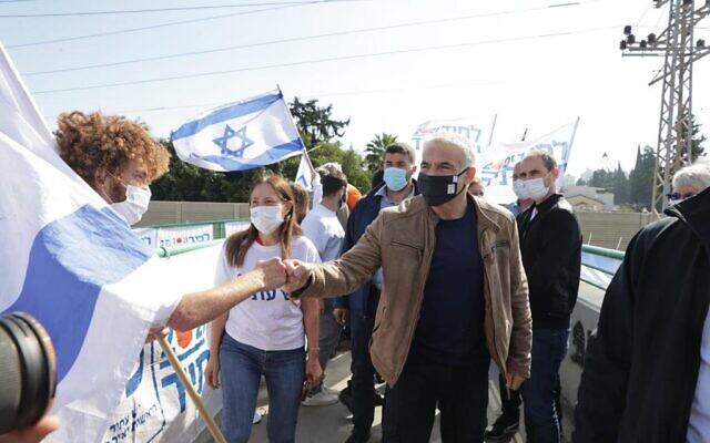 gente con máscara de un partido haciendo campaña, se ven bnderas de Israel