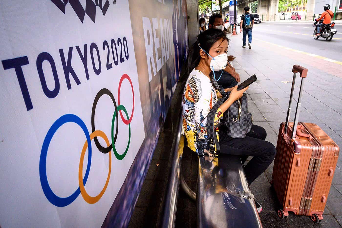 joven japonesa sentada frente a un anuncio de los juegos olímpicos de Tokio