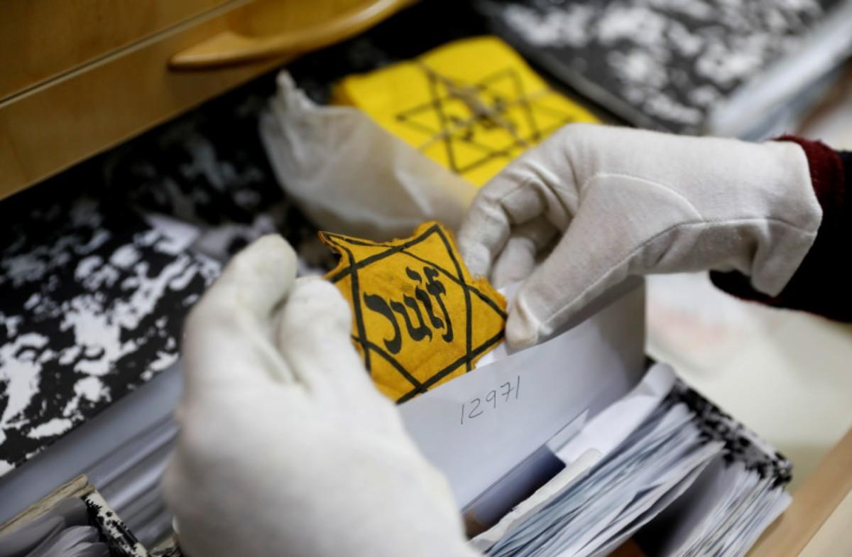 dos manos con guante blanco sujetan una estrella amarilla original del Holocausto entre los archivos