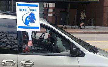 Cartel antisemita sostenido por el ocupante de un auto