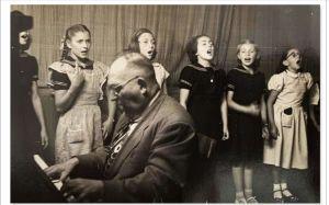 Moishe Yvker, al piano, en una de sus clases de música para un coro de niñas
