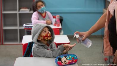 Niños reciben gel desinfectante en la escuela