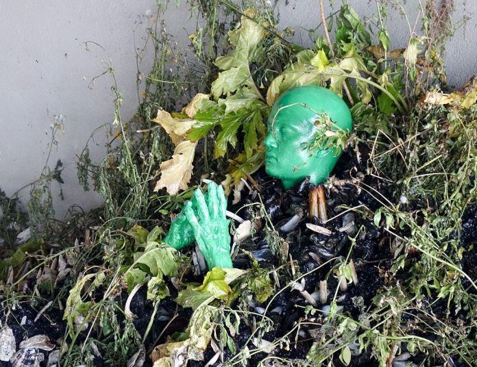 Le premier, verdâtre, est entouré d'une maigre végétation. Il parait surmonter les tentacules d'un céphalopode de coquilles…