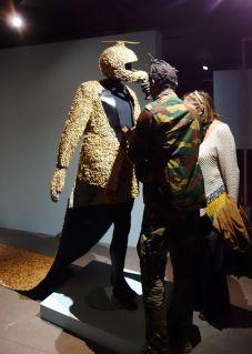 Yannick Makanka Tungaditu, dit Yannos Majestikos (né en 1988 à Kinshasa ; vit et travaille à Kinshasa) Sapekologie téléportation (2017-2018) Costume confectionné en tissu et en coques d'arachides