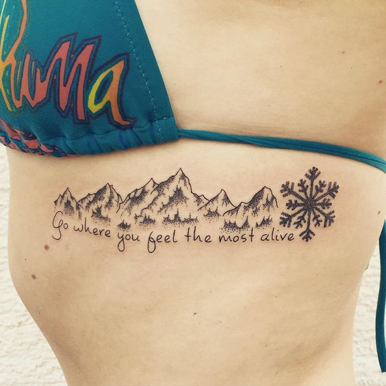 blackwork mountains snowflake quote tattoo on ribs