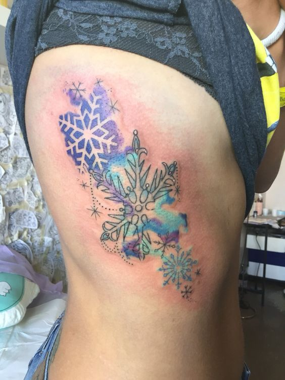 watercolor snowflakes tattoo on rib cage