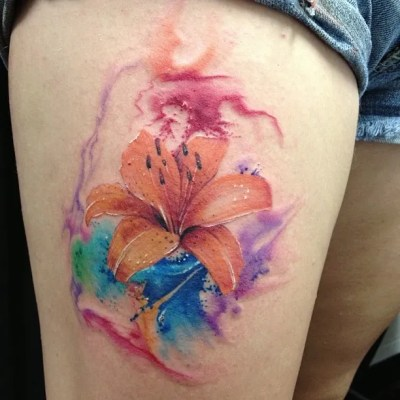 watercolor tiger lily tattoo on thigh