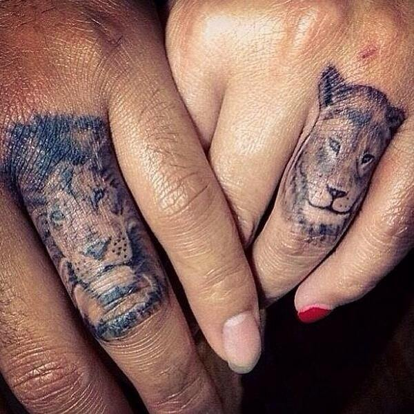 lion and lioness face tattoos on ring fingers for couples