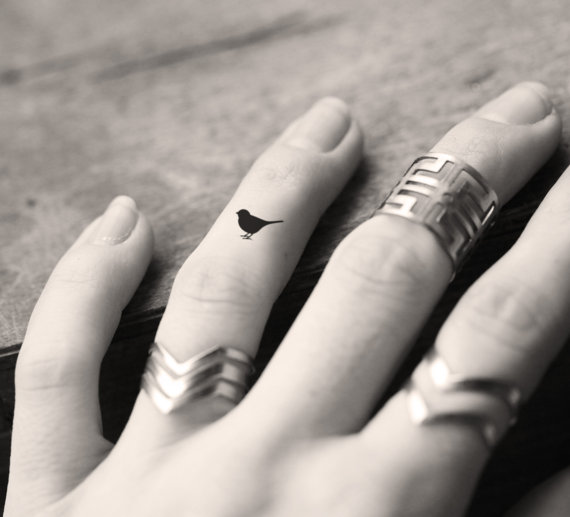 small bird tattoo design on ring finger