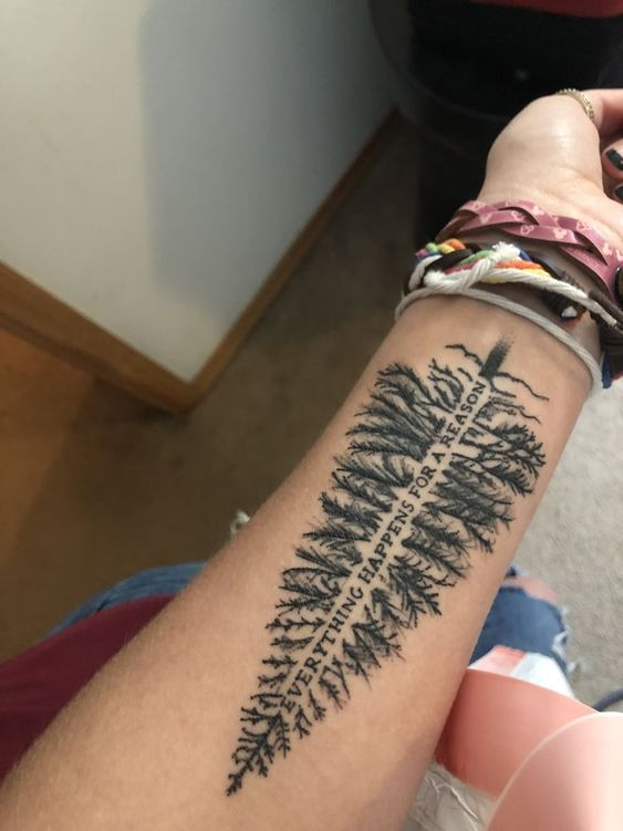 evergreen tree with quote everything happens for a reason tattoo on wrist