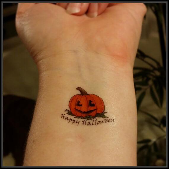 happy halloween pumpkin tattoo on wrist