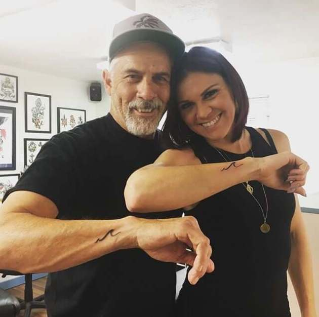 matching simple wave father daughter tattoos on side wrist