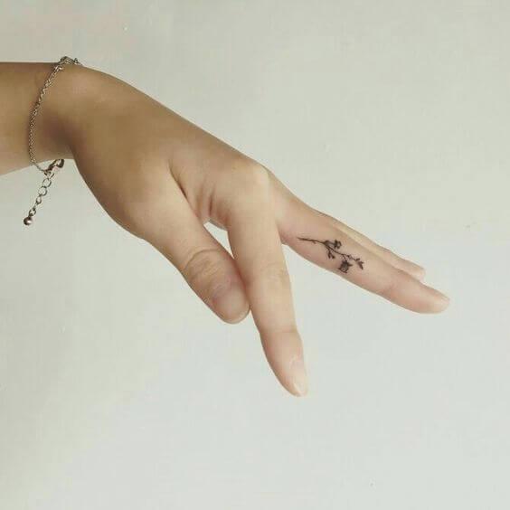 tiny lavender sprig tattoo design on side ring finger