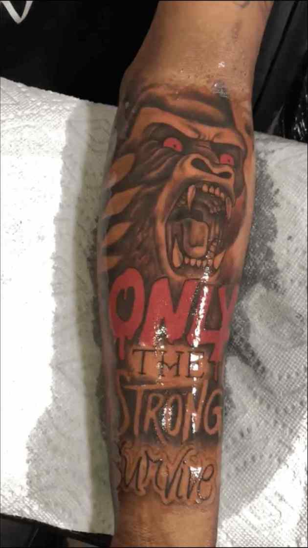 roaring red eyed gorilla with only the strong survive tattoo design on forearm