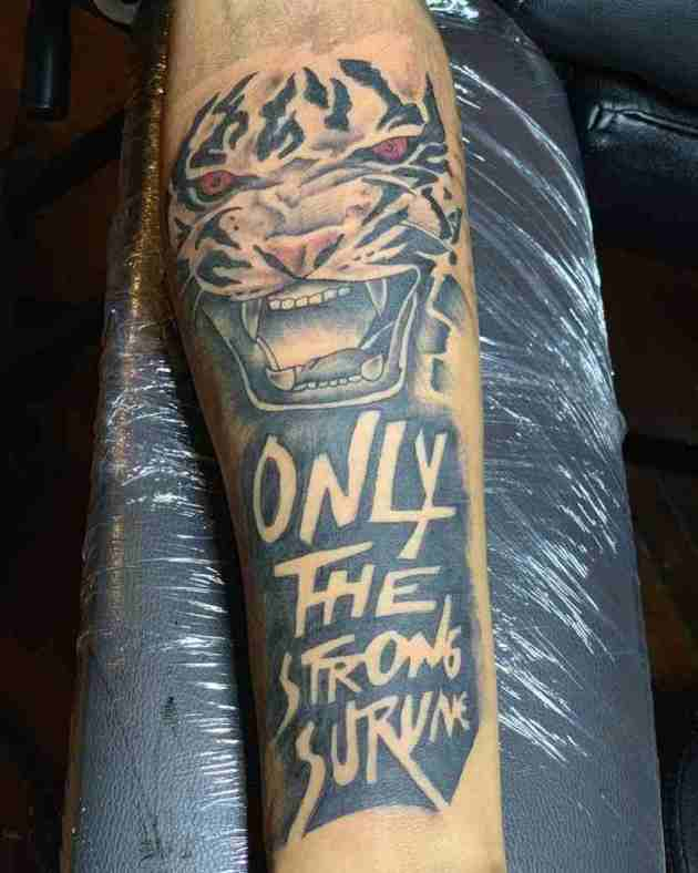 roaring tiger with quote only the strong survive tattoo design on forearm