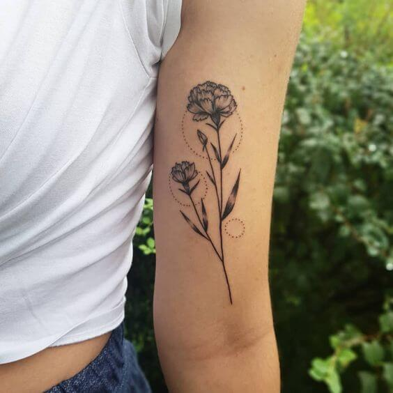 carnation January birth flower with dotted rings tattoo on upper arm