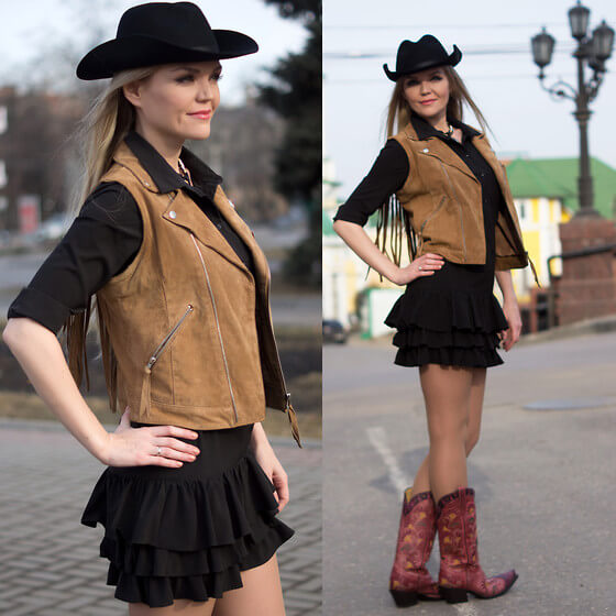 black ruffled mini dress with hat and camel vest with boots cowgirl outfit idea