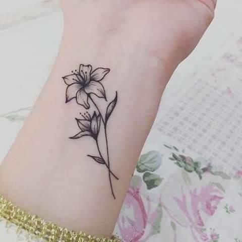 black and grey narcissus flower tattoo design on wrist