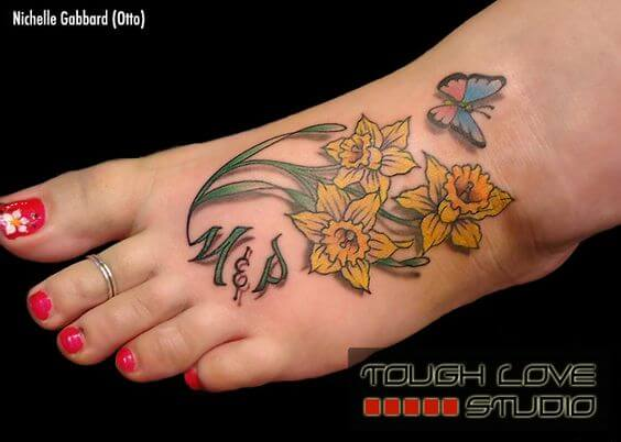 3d yellow narcissus flowers buds with initials and butterfly tattoo design on foot