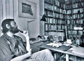Con pipa en su biblioteca sentado