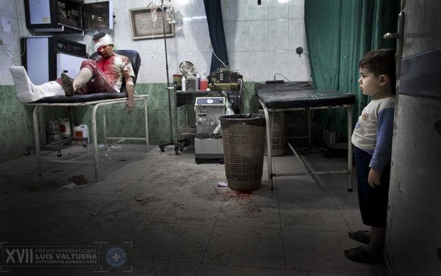 Un niño en el hospital Dar Al-Shifa mira a los pacientes heridos. El hombre herido fue llevado junto a su esposa, embarazada, al hospital. Ambos están en estado crítico. / Niclas Hammarström
