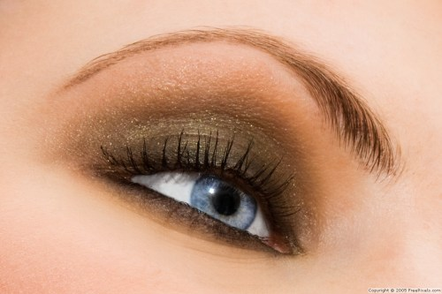 Beautiful woman eye with golden-brown cosmetic make-up