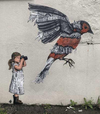 Street art depicting a girl photographing a bird