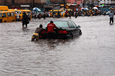 """A motorist needs help to """"swim"""" through a flooded Obafem Awolowo Way, Ikeja,       Lagos.  Lagos during rainstorm in pictures Stuck out there"""