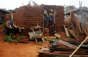 A woman stands helplessly beside her roofless home after a rainstorm in Lagos
