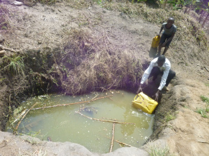 A man and his son fetching water from a shallow well in Kakiika, Mbarara district of Uganda  Worry over quality of surface water in Uganda a man and his son fetch water from a shallow well in kakiika mbarara district of uganda 300x225