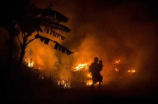A man carries his son through the haze on the way to his house as fires burn peatland and fields at Ogan Ilir in Palembang. Photo credit: Ulet Ifansasti/Getty Images