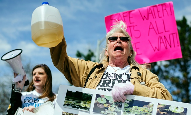 Protesters hold up jugs of discolored water outside the Farmers Market in Flint, marking the one-year anniversary of the city switching from using Detroit water to Flint River water. Photo credit: Sam Owens/AP  How Michigan's Flint River is poisoning the city's residents Michigan