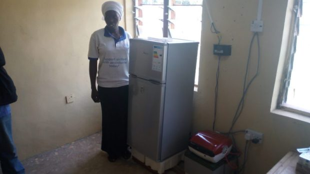 Aminichi Edwards, a Junior Community Health Extension Worker (JCHEW) at the Garaha Primary Healthcare Centre in Garaha Mojili, stands beside one of the two fridge-freezers provided the clinic. She says that, compared to before when the hospital had no such equipment, drugs and vaccines such as the Hepatitis B Vaccine can now be stocked and thus readily available for administration to newly born babies