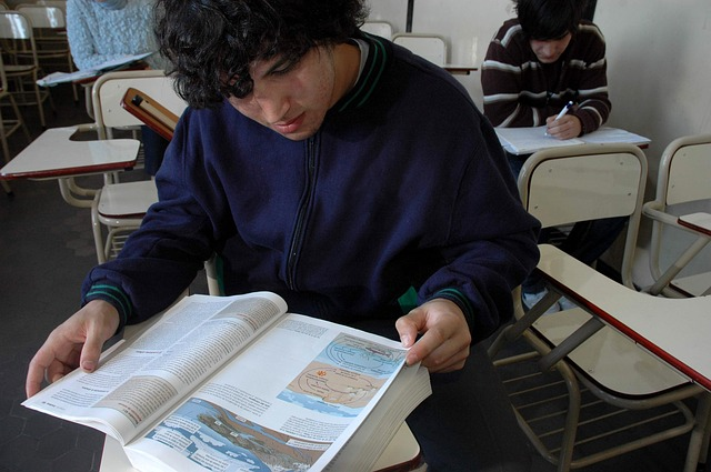 Student Examining a Textbook Reading the Pages at a Desk in a Classroom
