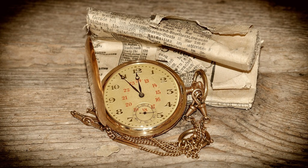 Folded old paper sitting on a wooden table with a gold antique pocket watch and pen laying in top