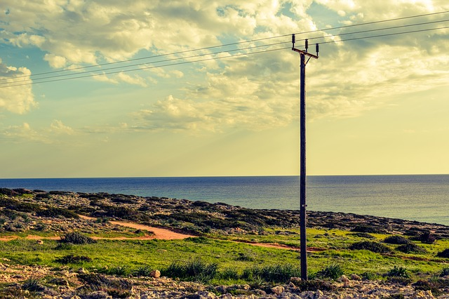Image of a telephone poll standing in front of the ocean