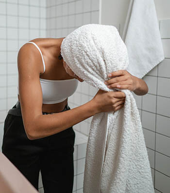 person wrapping hair in towel
