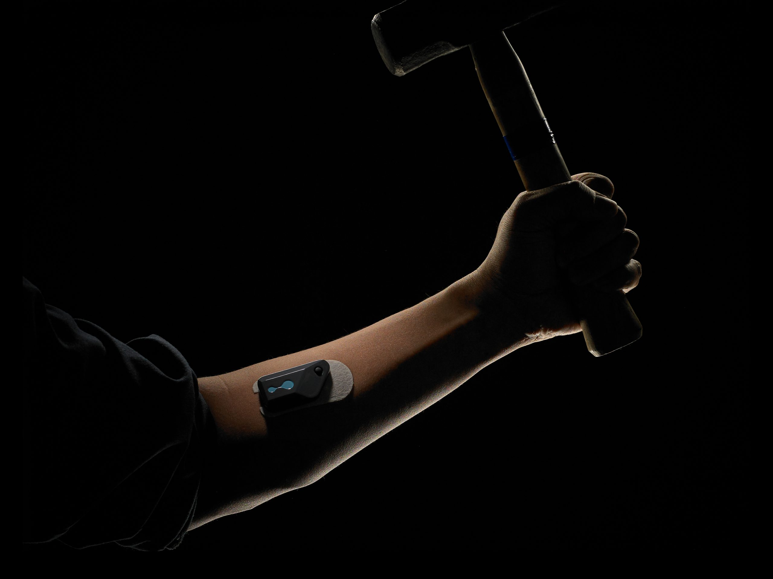 Image of Connected Hydration device on forearm of subject weilding a hammer