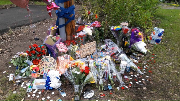 Flowers, even a teddy bear adorn the site of a fatal car accident