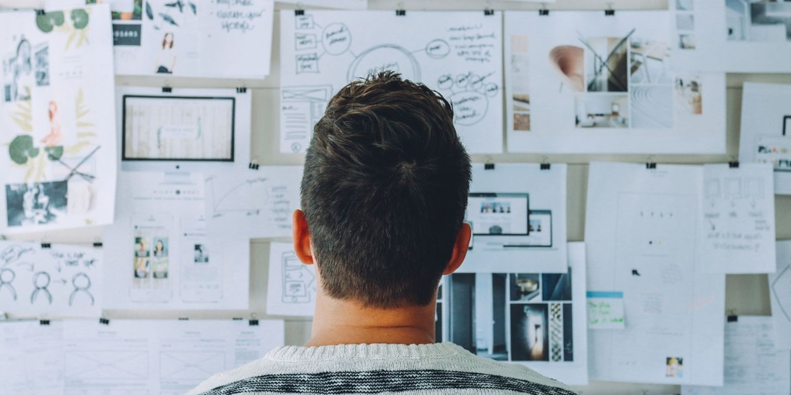 Image of man looking at a bulletin board.