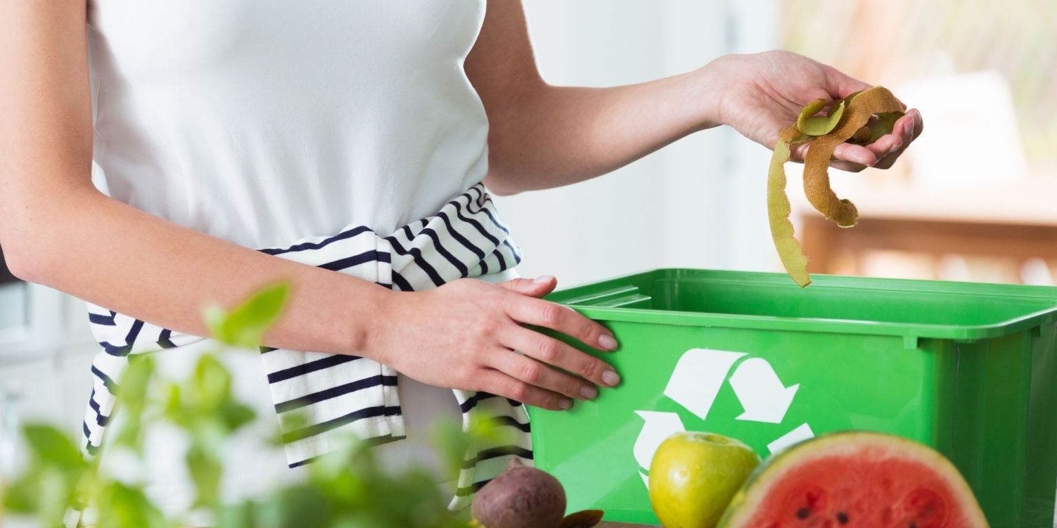 Image of woman putting food waste in a recycling container